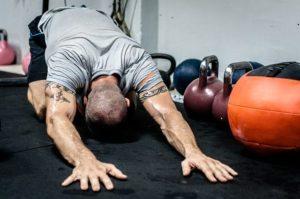 Mann bei Dehnung am Boden im Crossfit Training