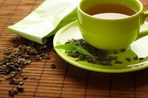 Photo Caption A cup of green tea on a bamboo mat with dried tea leaves Photo Credit Kasiam/iStock/Getty Images