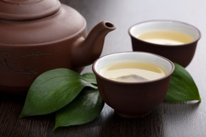 zwei Tassen mit grünem Tee und Teekanne mit Teeblättern