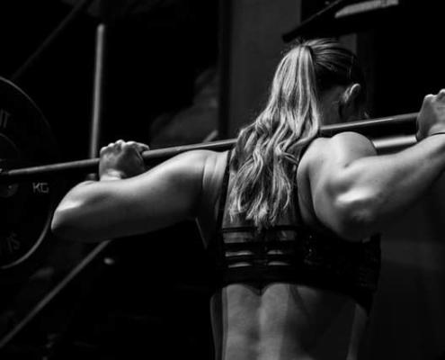 Frau mit Hantelstange im Nacken - Trainingsempfehlungen im Krafttraining Dogmen durchbrechen