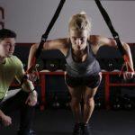 Frau mit Trainer bei Brustübungen Schlingentrainer
