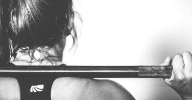 Frau beim schweren Training mit Hantel im Nacken