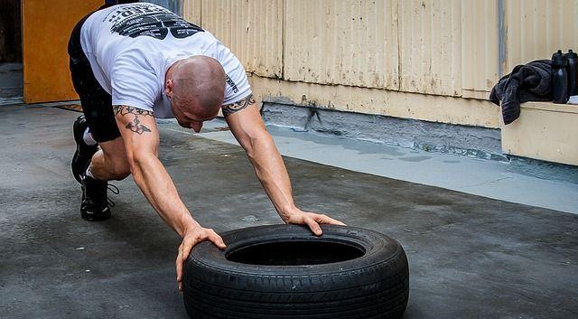 Mann trainiert am Reifen für seinen perfekten Sommerbody