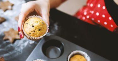 karotten mohn muffins in Frauenhand mit Muffinform