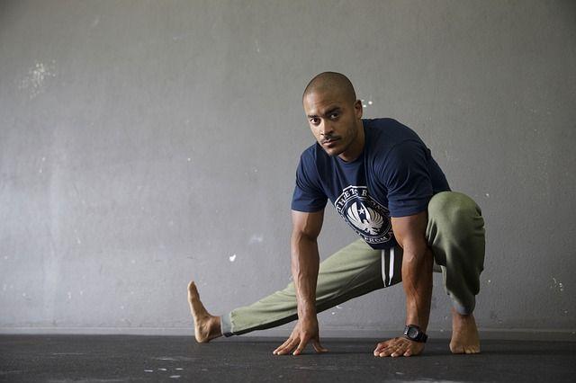 Mann beim Stretching: Satzpausen im Training sinnvoll füllen