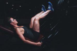 Frau auf Beinpresse: Geräte oder freies Training?