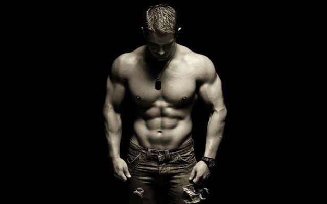 muskulöser Mann und die Frage: Geräte oder freies Training?