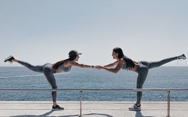 Frauen bei Balanceübung: Sport für Faule & Sportmuffel